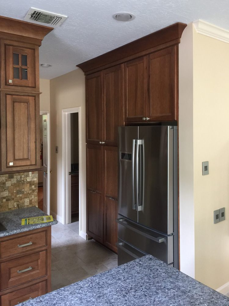 Stainless steel refrigerator and cherry pantry kitchen modeling.
